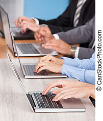 Close-up Of Businesspeople Using Laptop - Close-up Of...