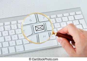 Looking at mail key through magnifying glass - Close-up of...