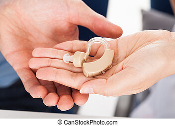 Hand Holding Hearing Aid - Close-up Hand Giving Hearing Aid...