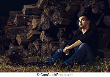 casual young man sitting outdoor near by railway