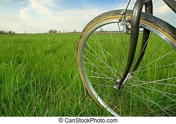Cycling - Bicycle wheel on a green field