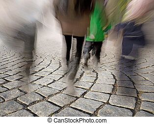 People walking on cobble stones - Legs of people in blurred...