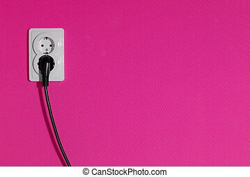 Socket - Cable connected into a power outlet on a pink wall