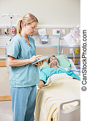 Nurse Using Digital Tablet While Patient Resting On Bed -...