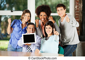 Teacher Holding Digital Table With Students Gesturing In...