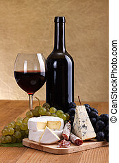 Red wine with cheese and blue grape snack. Large copy space...