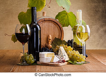 Red wine with cheese and blue grape snack in front of small...