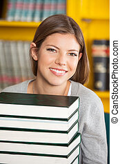 Beautiful Student With Piled Books Smiling In Library