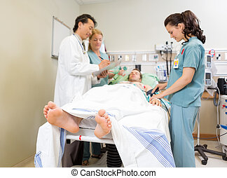 Medical Team And Patient In Hospital - Nurse examining...