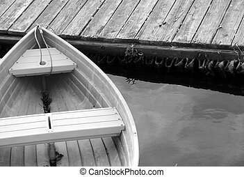 Rowboat at the pier - Peaceful scene of rowboat next to wood...