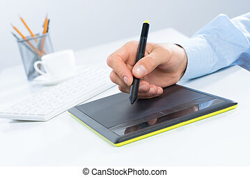Designer hand drawing a graph on the tablet which lies on a...