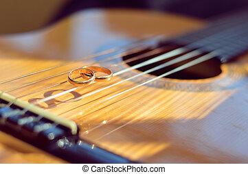 Wedding golden rings on guitar strings
