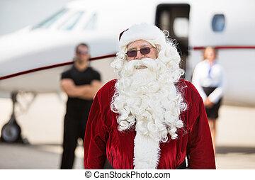 Man In Santa Costume Standing Against Private Jet - Portrait...