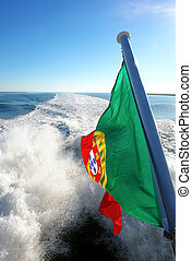 View of Lisbons river Tagus and Portuguese flag, Portugal...