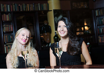 Two women drinking at an upmarket hotel - Two beautiful...