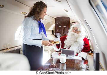 Smiling Airhostess Serving Cookies To Santa In Private Jet -...