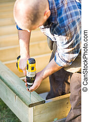 Carpenter Building Deck - Carpenter using cordless drill...