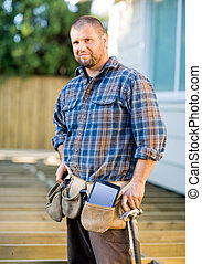 Carpenter With Digital Tablet And Hammer In Tool Belt At...
