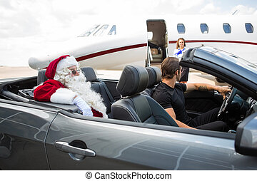 Santa and chauffeur in convertible while airhostess standing...