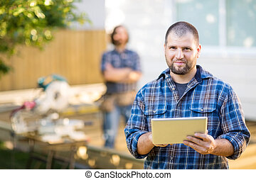 Portrait of mid adult manual worker holding digital tablet...