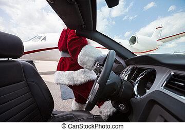 Santa Driving Convertible At Airport Terminal