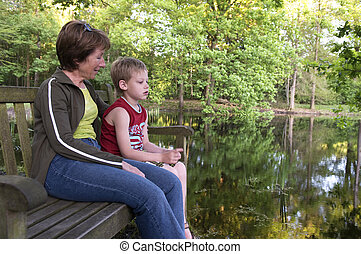 Sitting On A Bench - Grandma and her grandson are sitting on...