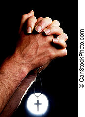 Praying Hands - Praying hands holding a cross in front of a...