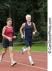 Running Seniors - senior couple running on a race track