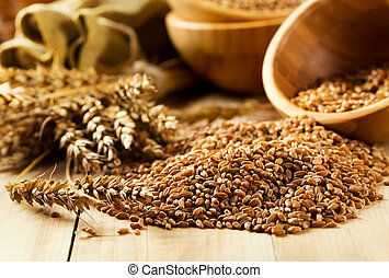 wheat grains - bowl of wheat grains on wooden table