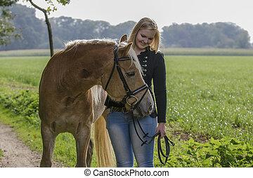 Spapziergang mit Pferd - Junge Frau macht einem Spaziergang...