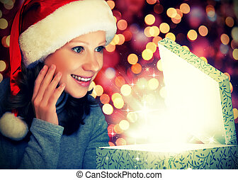 happy woman in a Christmas cap opens the magic box