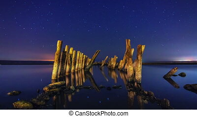 Timelapse of a starry night with wooden columns and firth...