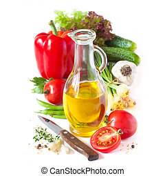 Olive oil and vegetables. - Jug of olive oil and fresh...