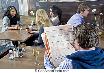 Cafe scene - A man reading a financial paper with several...