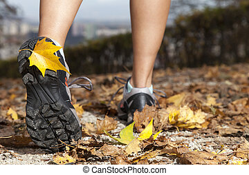 Feet of a runner in autumn leaves - Feet of a runner running...