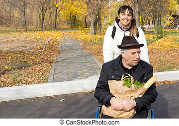 Smiling woman pushing an old man in a wheelchair