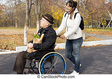 Happy woman helping a disabled elderly man as she pushes his...