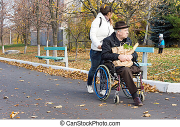 Carer pushing a disabled man in a wheelchair