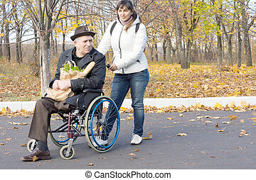Woman helping a disabled pensioner in a wheelchair pushing...