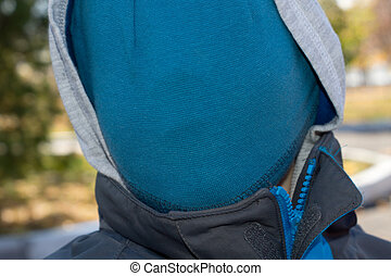 Person with a hidden face concealed under a blue knitted...