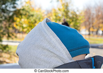 Person concealing their face under a blue fabric sitting...