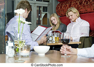 Chosing from the menu - A group of people looking at the...