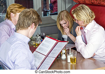 Chosing from a menu - a group of four people chosing dishes...