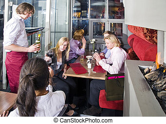 Waiting tables - A waiter serving customers at tables in a...