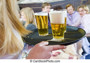 Three beers - A long haired blond waitress bringing a tray...