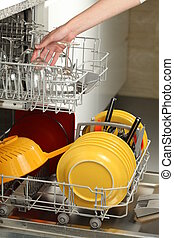 Housekeeping - Filling the dishwasher in a modern kitchen
