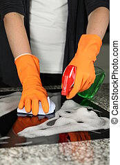 Cleaning a stove - Womans hands cleaning a kitchen stove,...