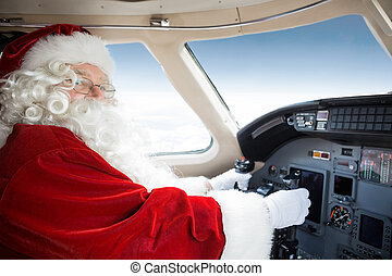 Santa Holding Control Wheel In Cockpit Of Private Jet -...