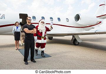 Santa Waving Hand Against Private Jet - Santa waving hand...