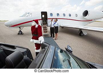 Santa walking up to private jet - Santa leaving convertible...